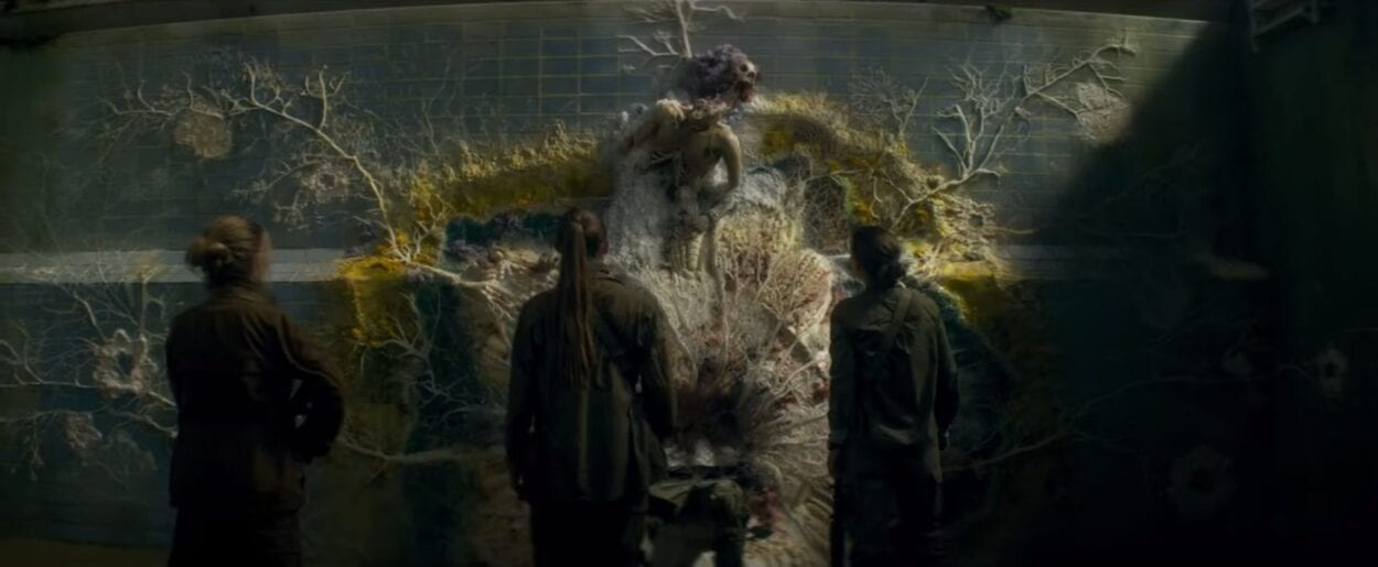 Three characters from Annihilation look on at a body, split at the waste. The top half sits a yard above the bottom half. A ring of moss, flowers and vines circle the body, supporting it.
