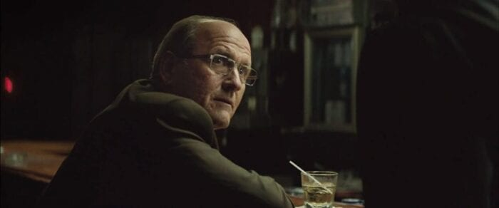 Richard Jenkins' unnamed spokesman hears out Jackie Cogan in a bar.