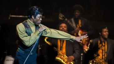 James Brown leans towards a captive audience clutching a microphone and stand.