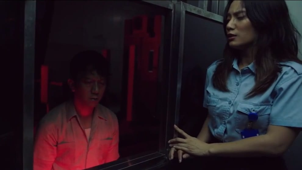 Maya looks frightened and confined in a booth as a harrowed looking man approaches her toll booth window.