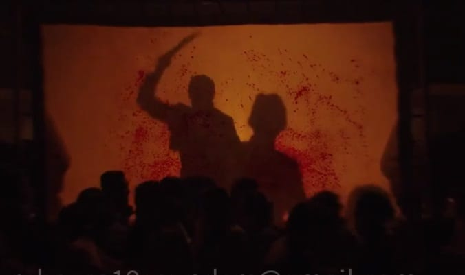 Shadows of a man attacking another with a machete appear on a blood soaked screen as a crowd of people scrambles in foreground.