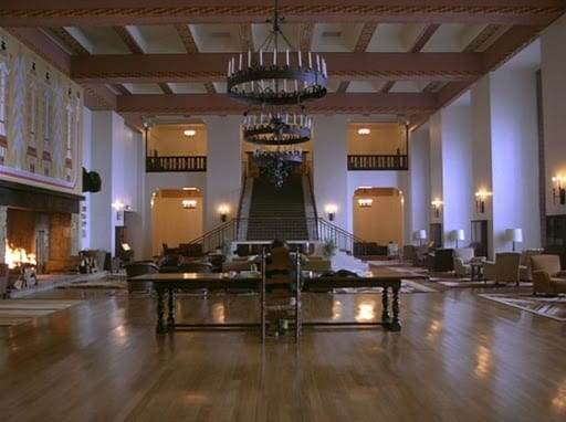 Long view of Overlook Hotel lobby as Jack Torrance sits in a highbacked chair working on writing.