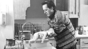 Jack washes baby Sarah under the kitchen tap