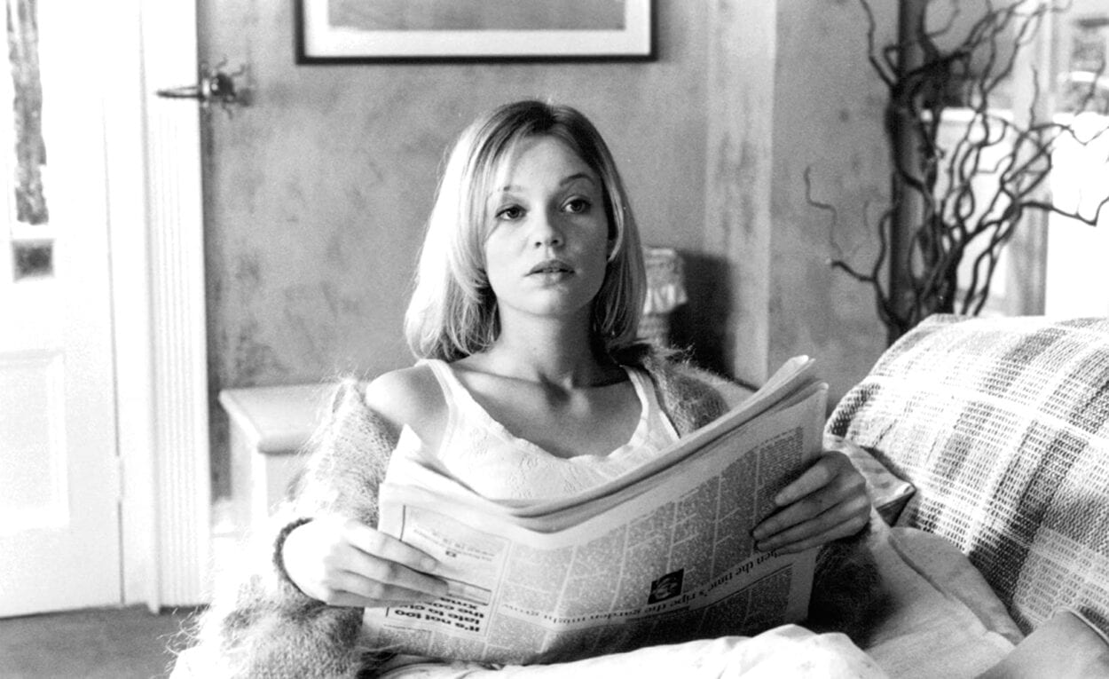 Amy, Samantha Mathis, reads a newspaper sitting on a couch