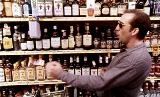 Nic Cage as Ben dancing as he adds bottles of alcohol into his shopping cart