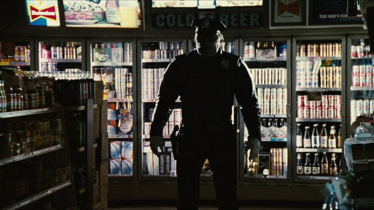 The Maniac Cop stands in silhouette inside a convenience store