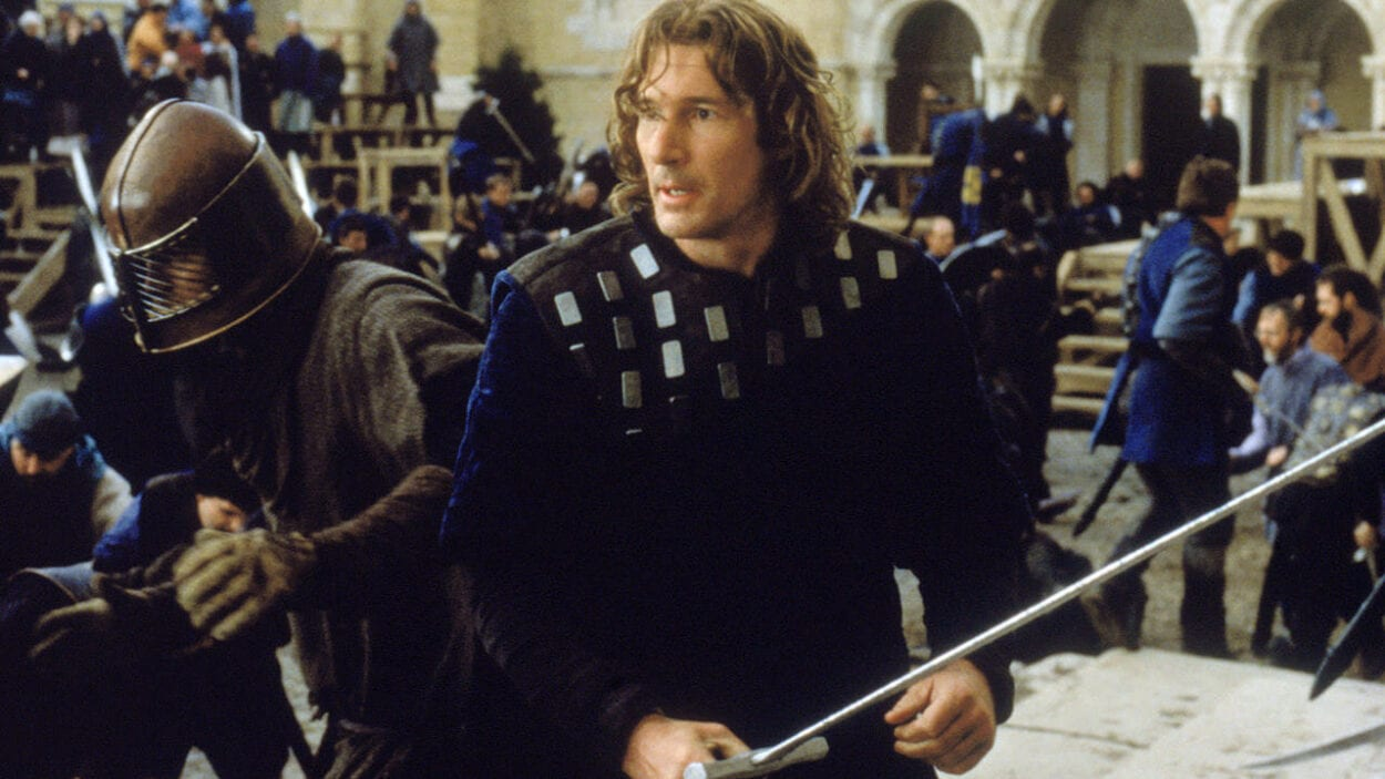 Lancelot has his sword ready for a duel with a battle raging around him