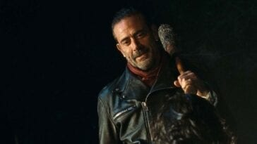 Negan smiles and holds his bat Lucille over his shoulder at night