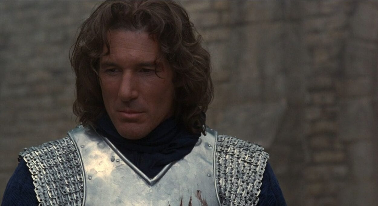 Lancelot stands thinking of a memory while wearing his armor