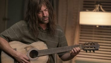 Graham Husker (Mark Duplass) playing guitar