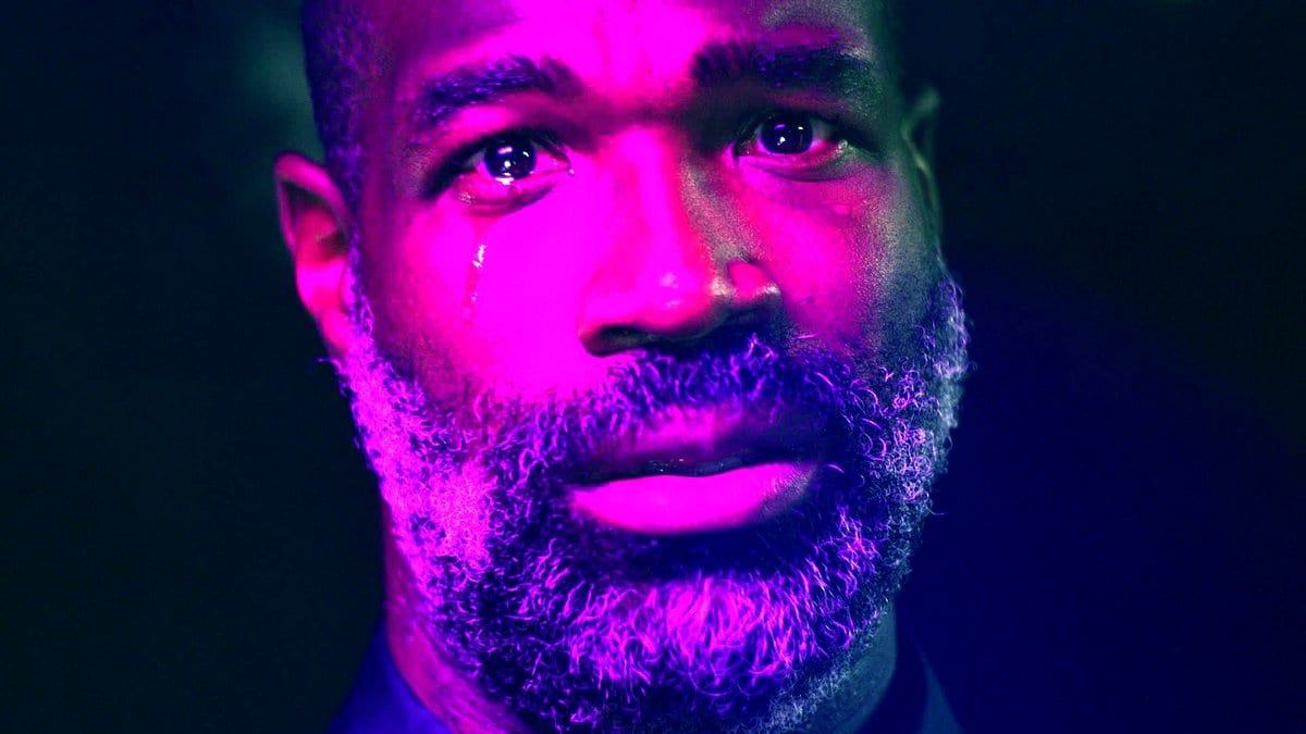 Tunde Adebimpe looking at the camera crying while bathed in a purple otherworldly light