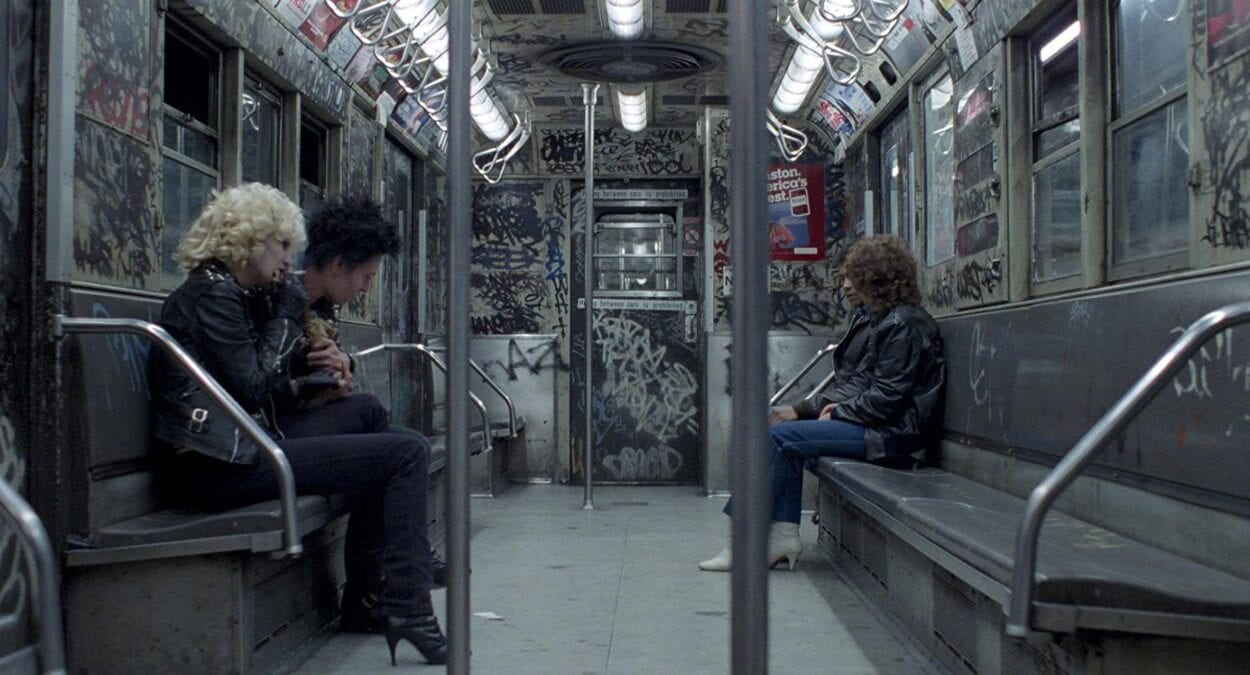 Sid and Nancy sit together on a subway train