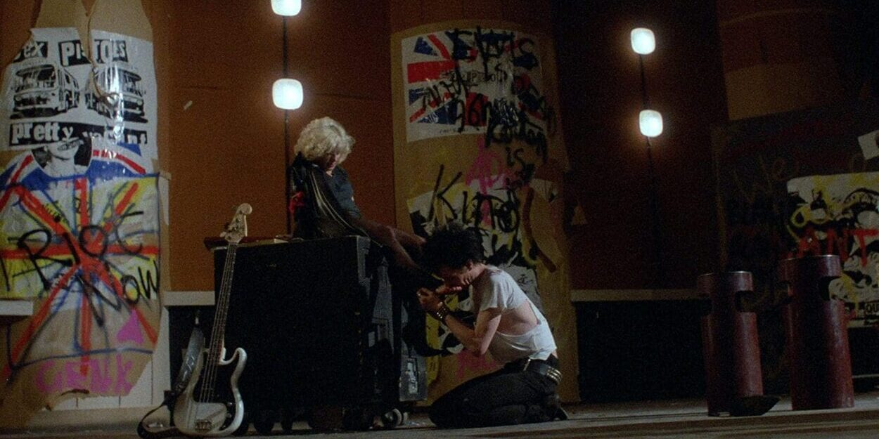 Sid kisses Nancy's feet as she sits on an amplifier