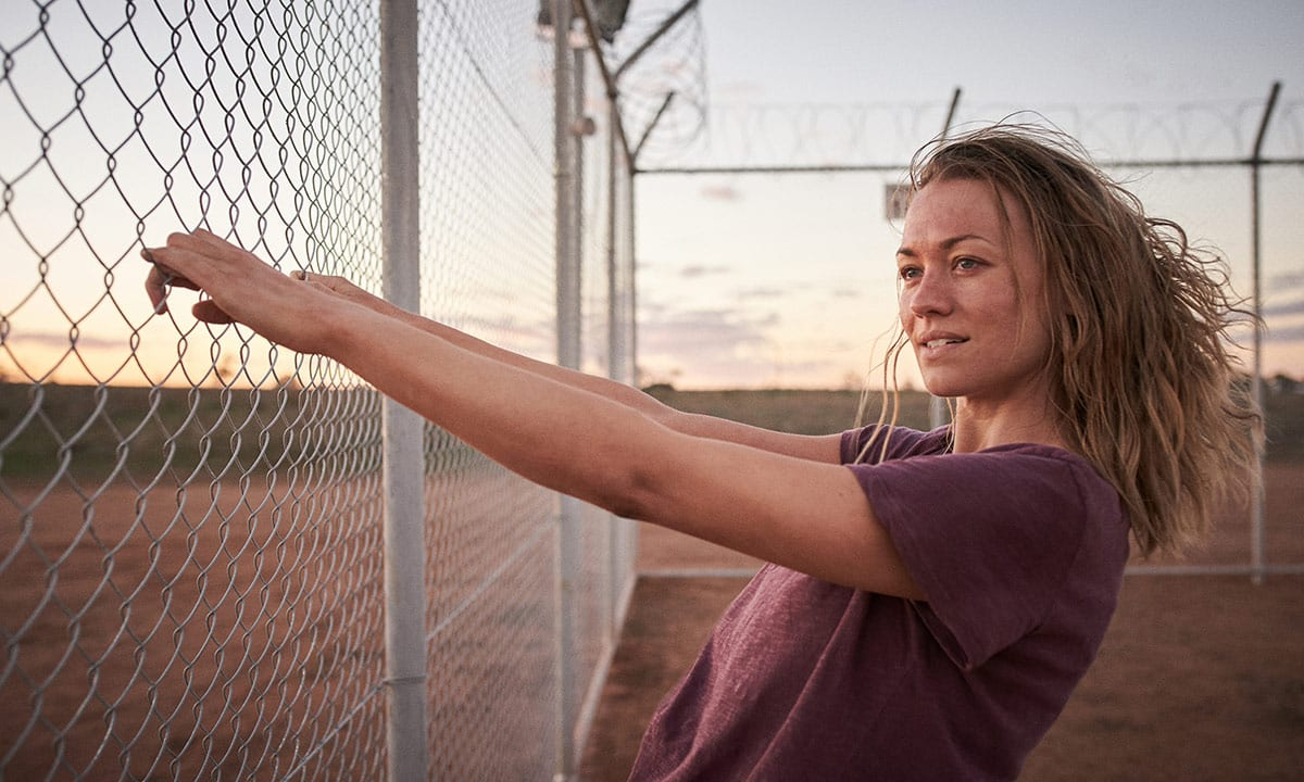 Sofie holds a fence in Barton Detention Center in Stateless
