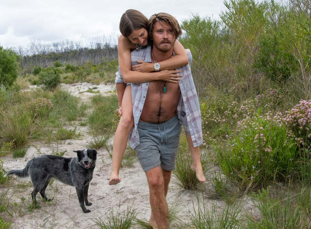 Lu carries Georgie by piggyback down to a beach accompanied by a dog.