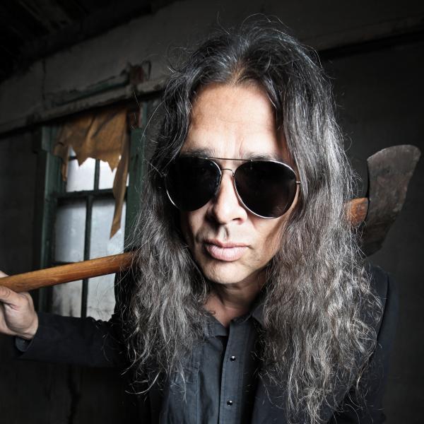 Photograph of author Stephen Graham Jones wearing dark aviator shades with an axe slung over shoulder.