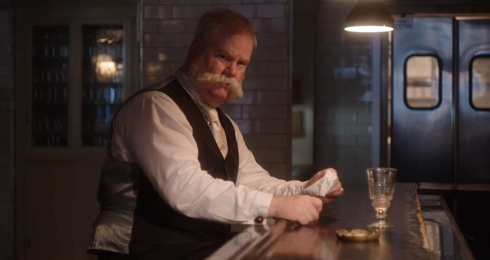 George Westinghouse (Jim Gaffigan) sits at a bar drinking a glass of lemonade. His mustache is large and white.