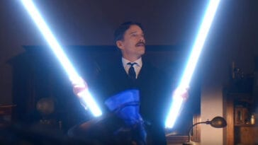 Nikola Tesla (Ethan Hawke) holds up two long light sticks, admiring them.