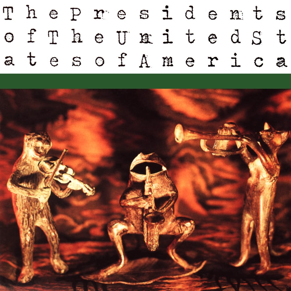 On white at the top is black typerwriter font of the band's name, and the bottom two thirds are three gold figurines as follows: a bear playing fiddle, a toad playing saxophone, and a cat playing trumpet.