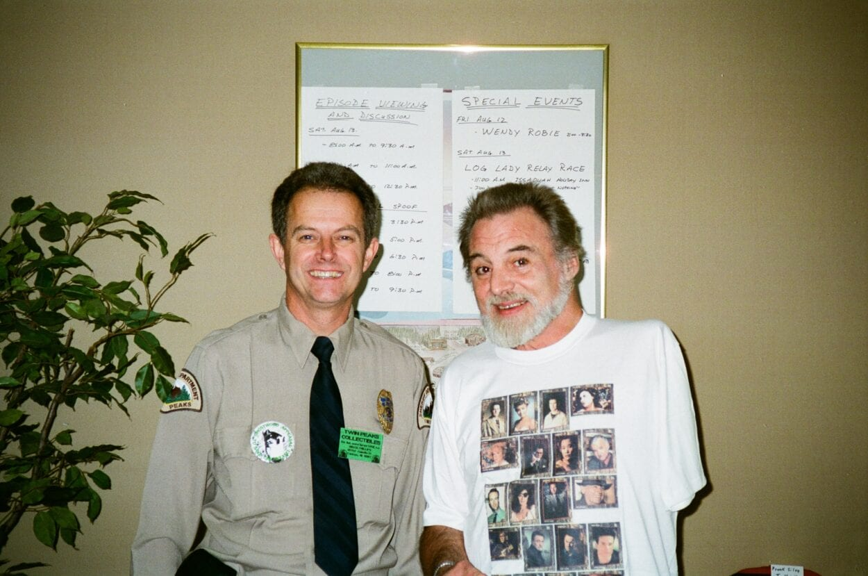 Picture of Bruce Phillips dressed as a Twin Peaks Deputy, posed next to Al Strobel