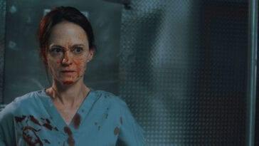 Mandy (Angela Bettis) stands in the morgue of a hospital in blood-stained scrubs.