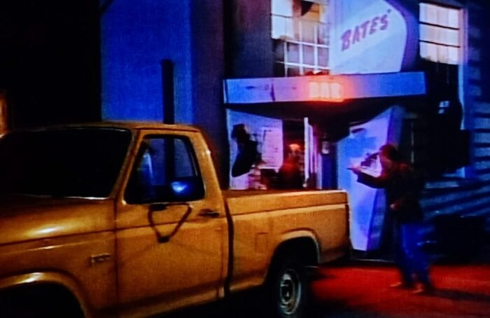 A pickup truck sits outside of Bates' Bar where a man leaving points fervently at a another man entering