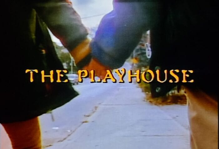 "Two children walk hand-in-hand down a suburban sidewalk. The episode's title, ""The Playhouse"" is displayed."