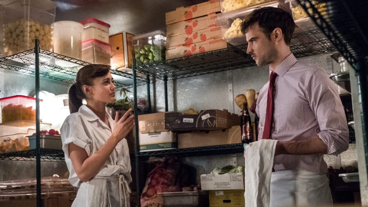 Tess and Jake stand in the walk-in fridge surrounded by ingredients.
