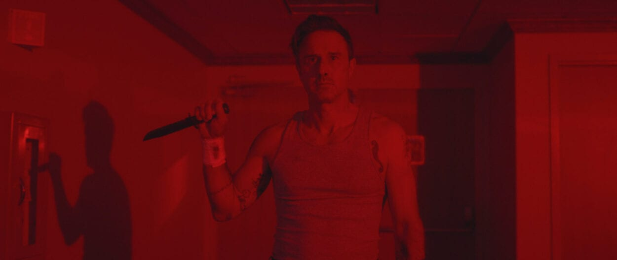 Jefferson (David Arquette) stands holding a knife in a red-lit room, wearing a wife beater.