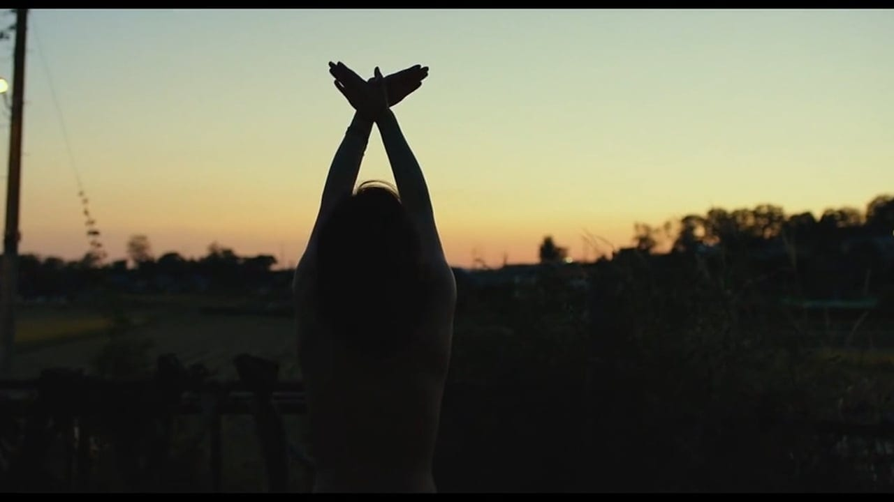 Haemi raises her arms to the sky, facing the sunset.