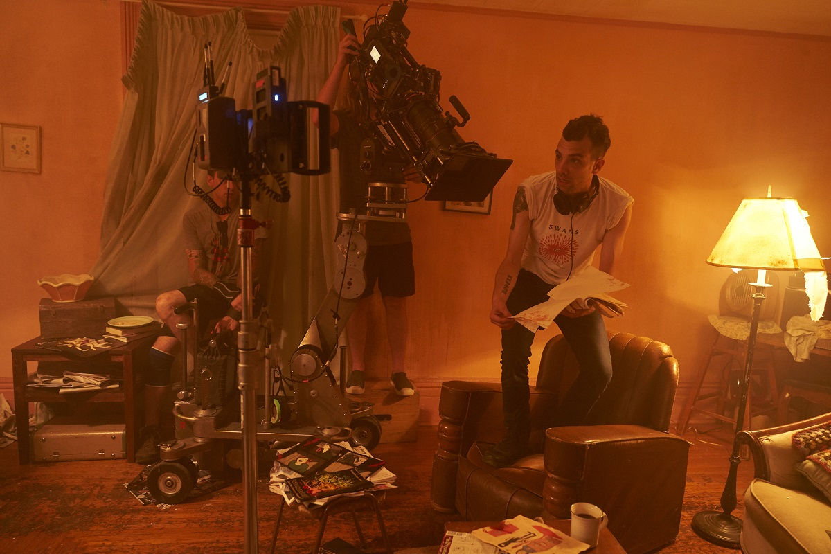 Jay Baruchel stands on a chair giving direction.