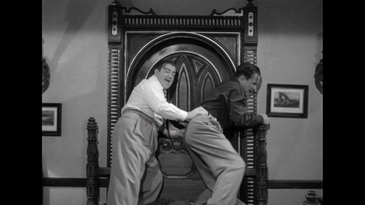 """Wilbur Grey (Lou Costello) and Chick Young (Bud Abbott) brace their shoulders against a door as they barricade it with a bed in the film, """"Abbott and Costello Meet Frankenstein"""" (1948)."""