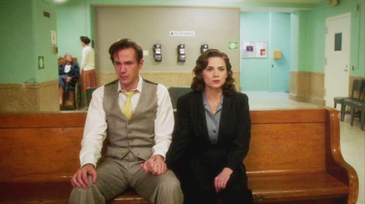 """Edwin Jarvis (James D'Arcy) and Peggy Carter (Hayley Atwell) hold hands sitting in a hospital waiting room in """"Agent Carter"""""""