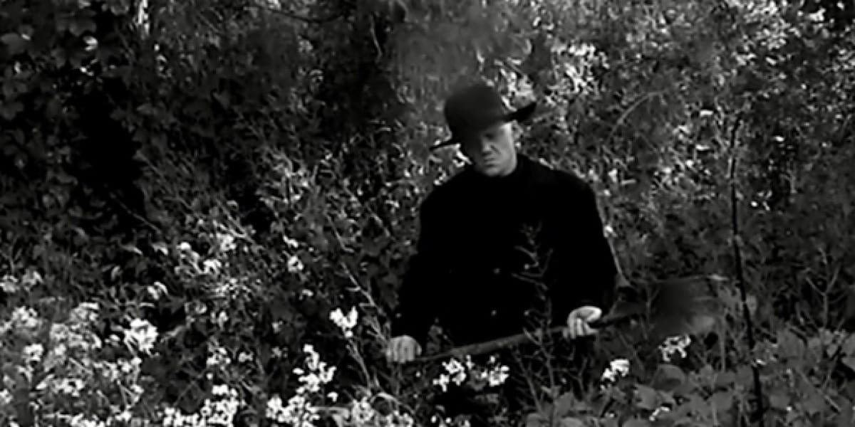 Man holding a shovel in graveyard