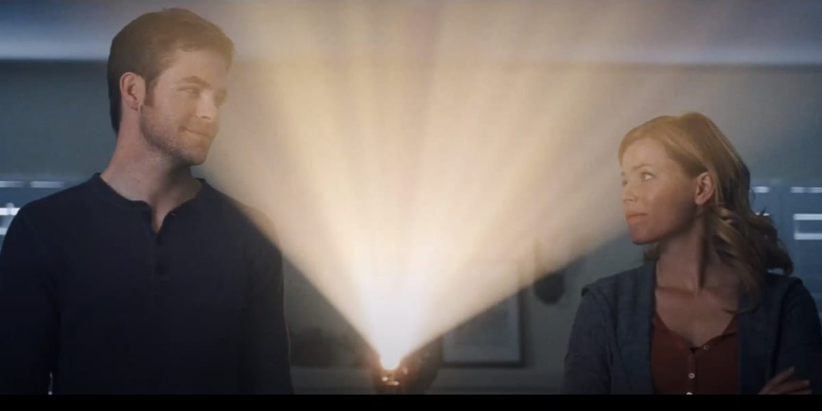 Sam and Frankie looking at each other warmly, Frankie a bit teary-eyed, with a projector light shining between them in the ending of People Like Us