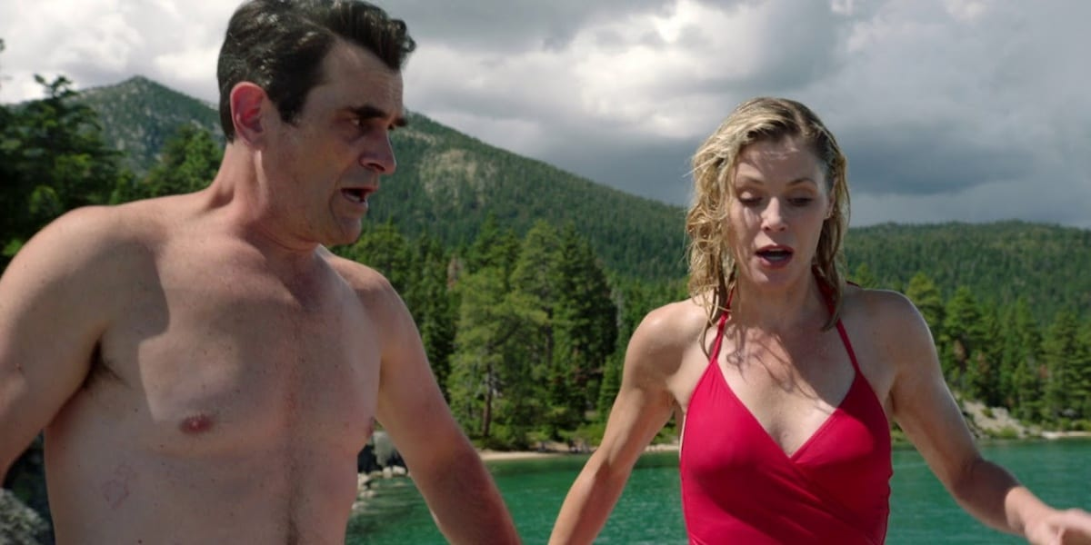 Claire and Phil in Modern Family, Claire and Phil holding hands, Claire's other arm held tensely to her left side as she looks down in fear, wearing a red swimsuit, Phil is shirtless and looking to his side, towards Claire, also looking afraid