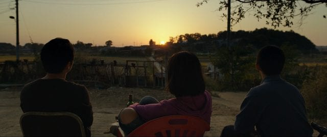 The three characters watch the sunset together with their backs to the camera