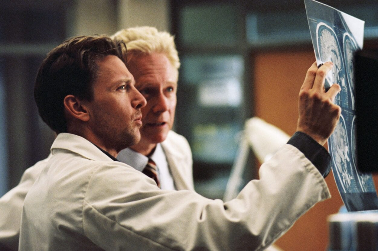 a blond doctor and a younger brown-haired doctor both intently study an x-ray film held up to the light