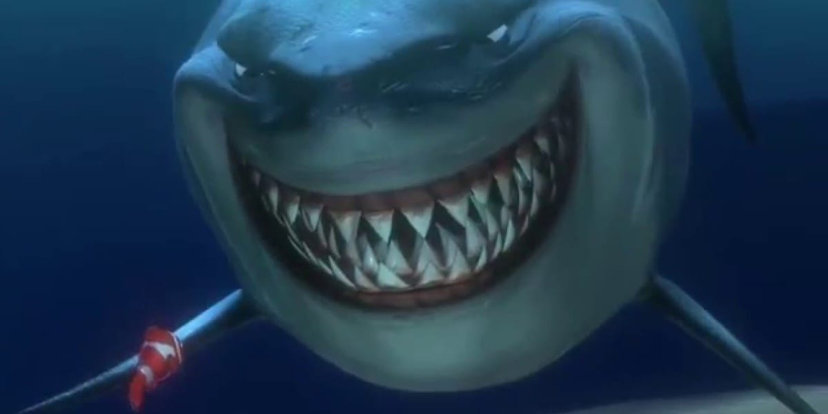 A smiling shark, Bruce, terrifies the living daylights out of Marlin, the clownfish with his back to the photo while under the sea in Finding Nemo