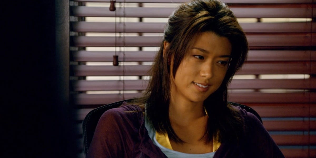 Kono in Five-0, wearing a purple jacket and smiling, looking downwards to her left, in Hawaii Five-0 with a window covered by blinds in the background