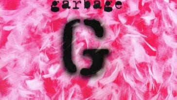 Cutouts of a letter G are spraypainted and are on top of a pink background littered with white feathers.