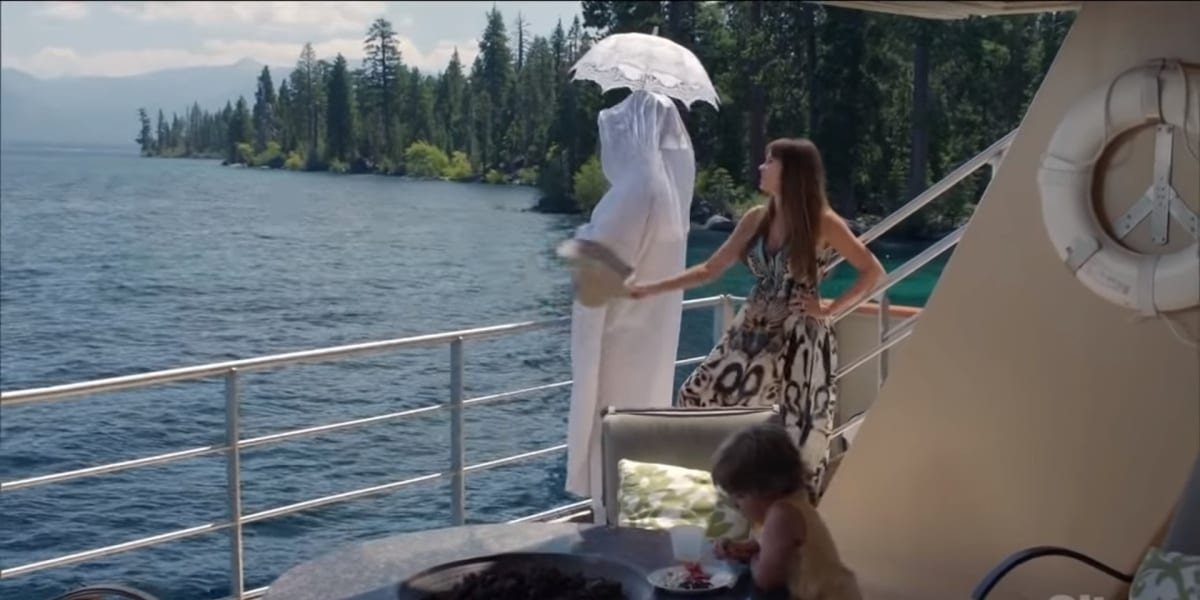 Cam wearing a white outfit and holding an umbrella, looking over the railing, with Gloria looking ahead in disdain holding out her hat, Joe in the forefront looking at his plate in Modern Family