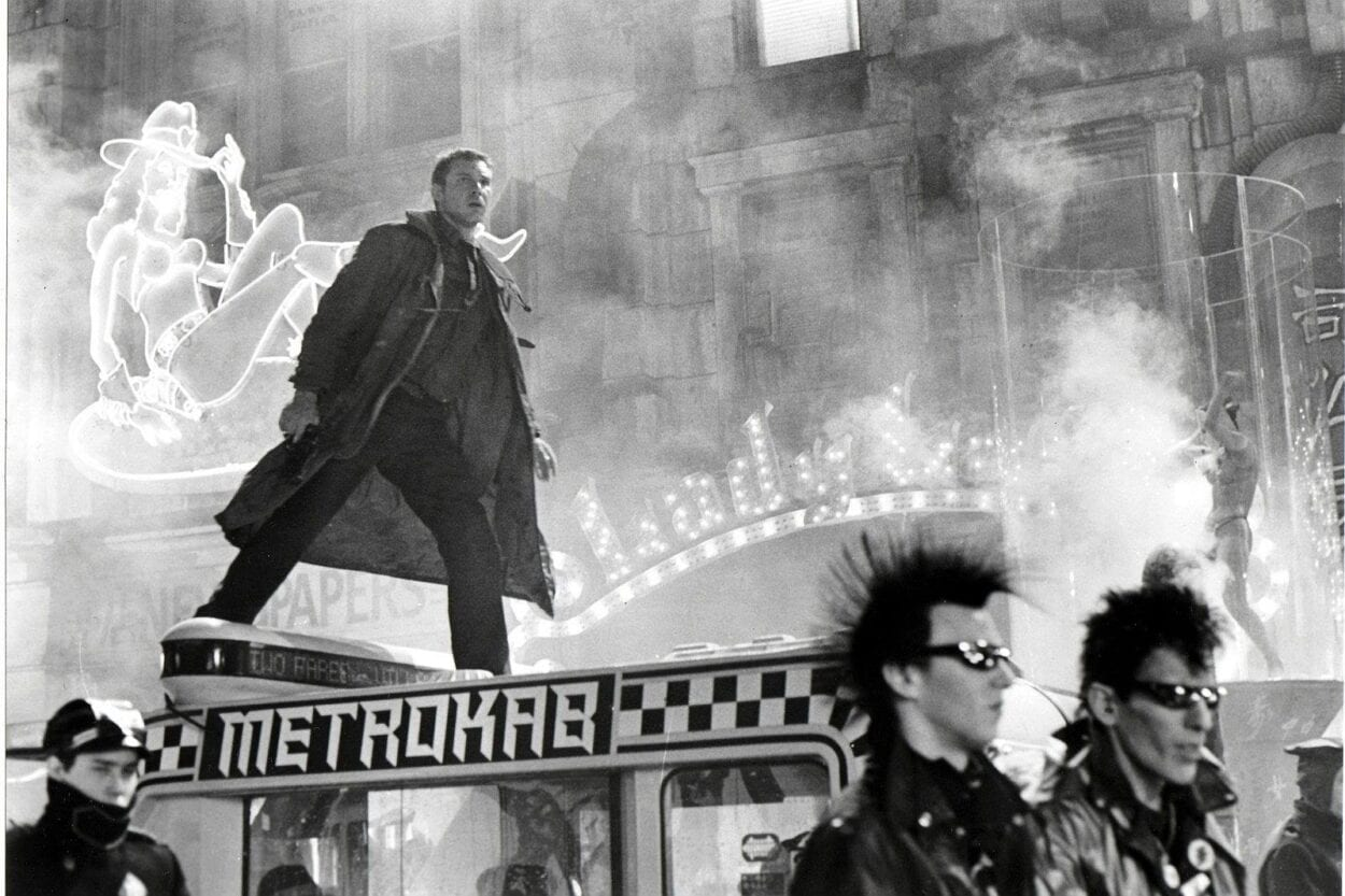 Harrison Ford as Deckard on top of a vehicle in Blade Runner