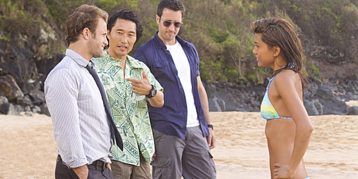 Kono in a bikini with her hands on her hips looking at Chin, who's introducing Danny to his left and Steve stands on the right wearing sunglasses in Hawaii Five-0