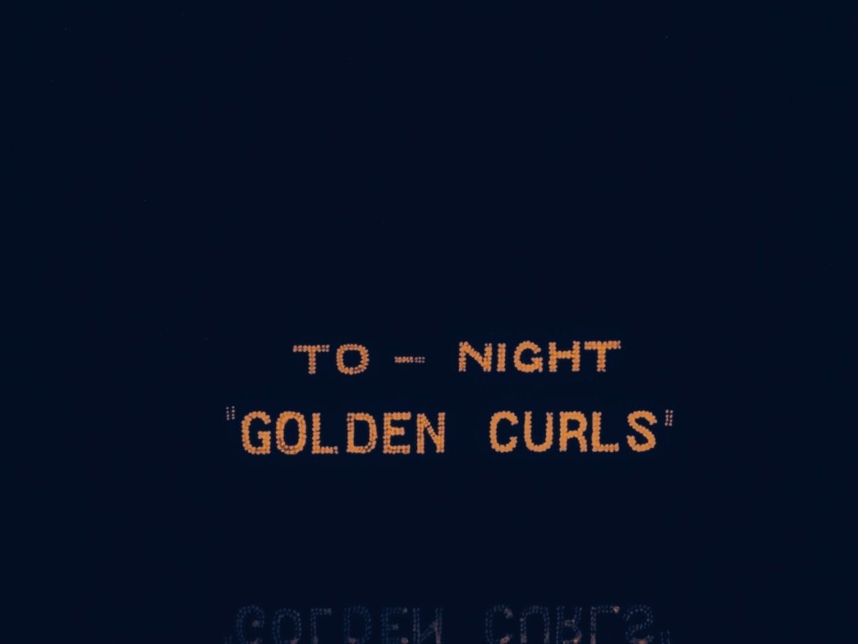 A sign advertises a show: Golden Curls