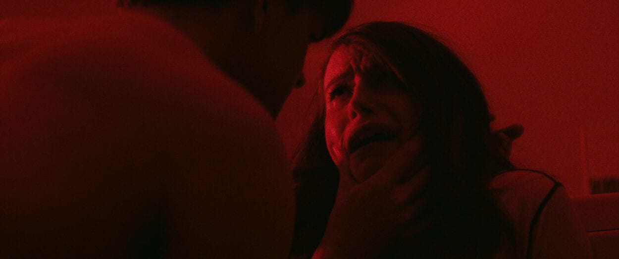 Tom (Jim Schubin) grips Eve's (Chloe Carroll) crying face in a red-lit room.