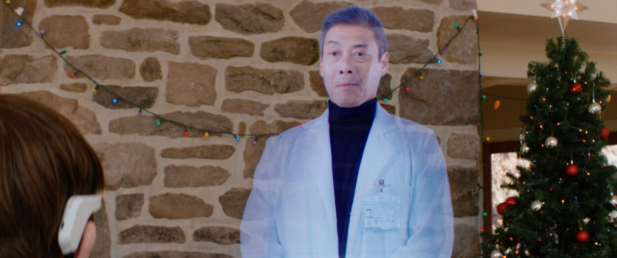 The Director (François Chau), a hologram, stands in front of a stone fireplace and Christmas decorations, addressing the couple.