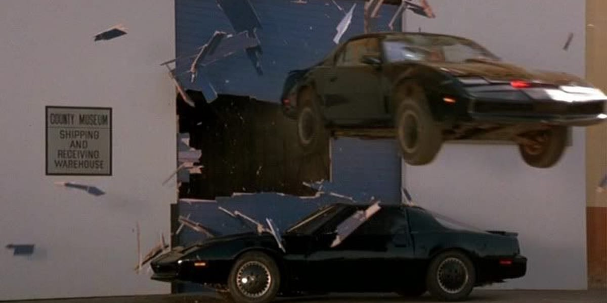 KITT jumps over another car just like him, smashing through a blue warehouse door in Knight Rider