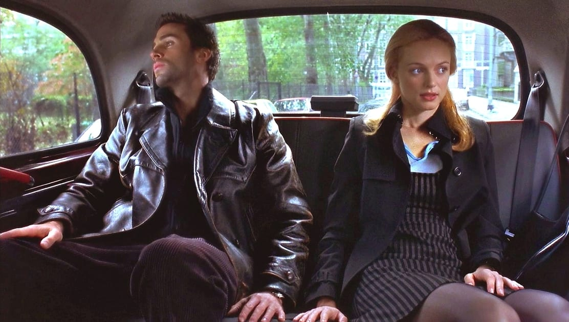 Alice and Adam sit silently in the back of a London taxi