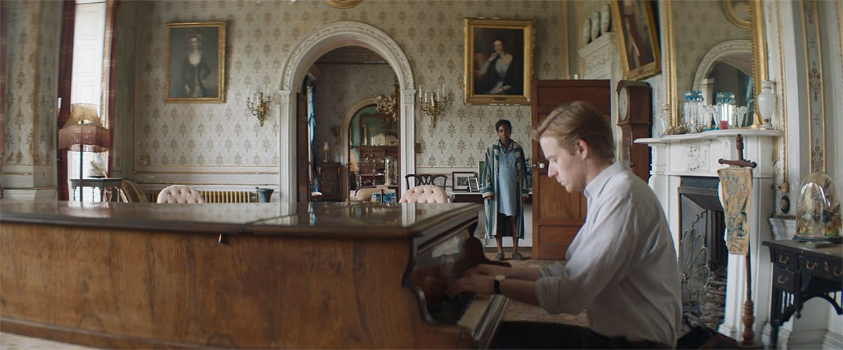 Thomas plays the piano as Charlotte looks on